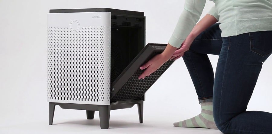 Woman replaces air filter in the air purifier.