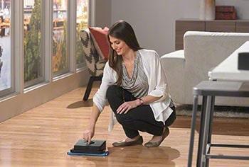 Woman starts the robot mop.