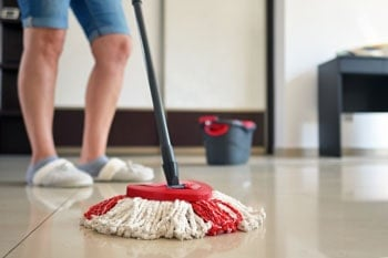 Woman mops the sealed floor.