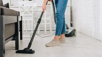 Woman vacuums the floor.