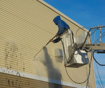 Man wash a house from the aerial platform.