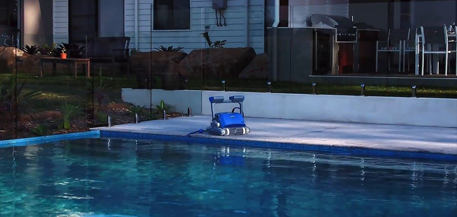 The ready to work robotic pool cleaner near the pool.