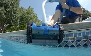Man with a suction pool cleaner.