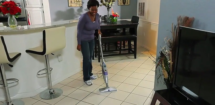 A woman cleans the ceramic floor with a steam mop.