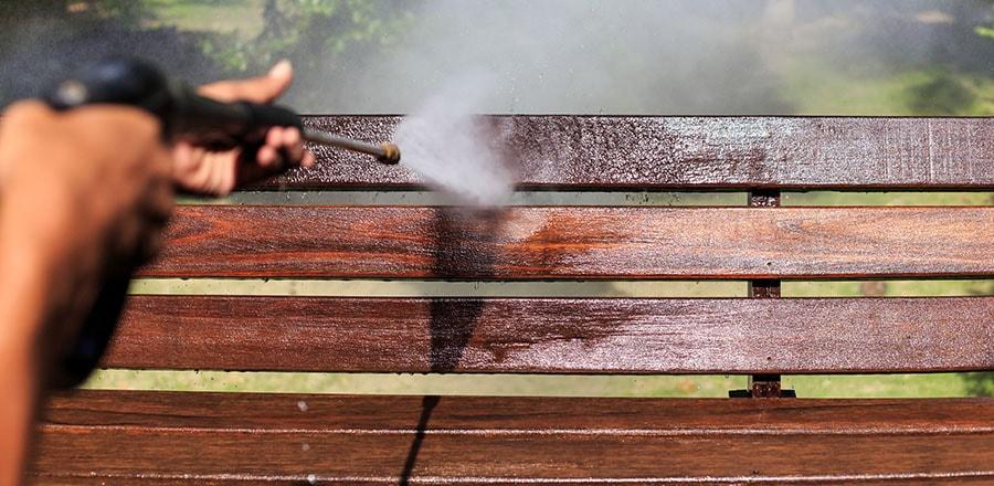 Man washing the garden bench.