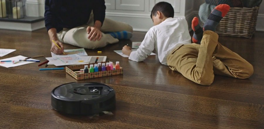 Robot vacuum does its duty near the father and a boy playing together.