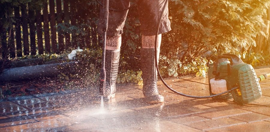 Man wearing protective boots while using pressure washer.