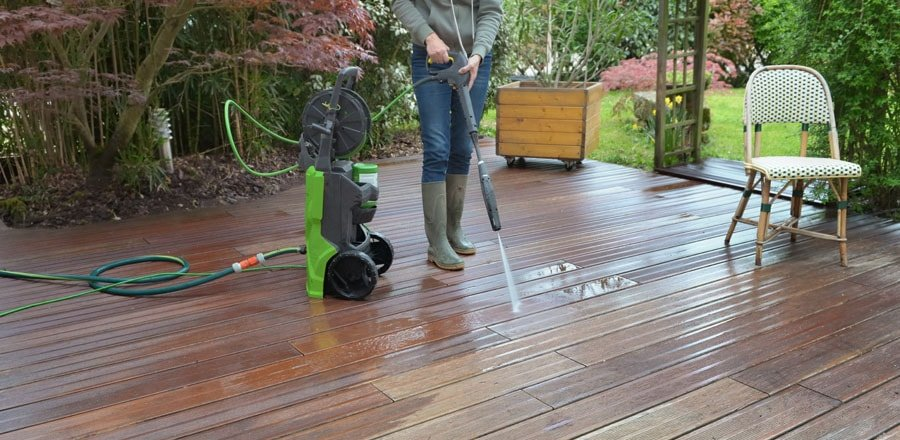 Man cleans his patio with an electric pressure washer.