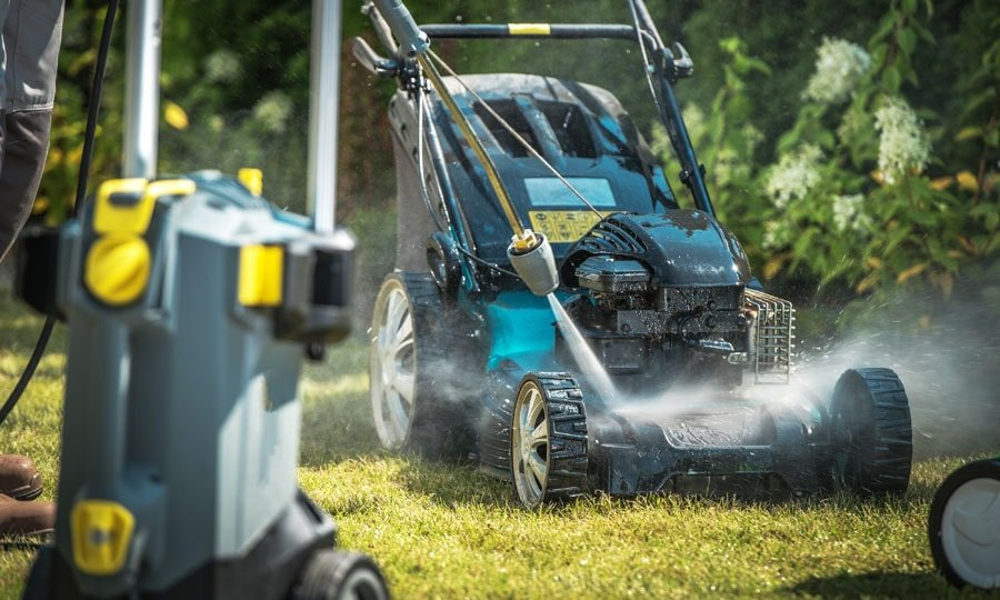 Man washes his lawnmower using electric pressure washer.