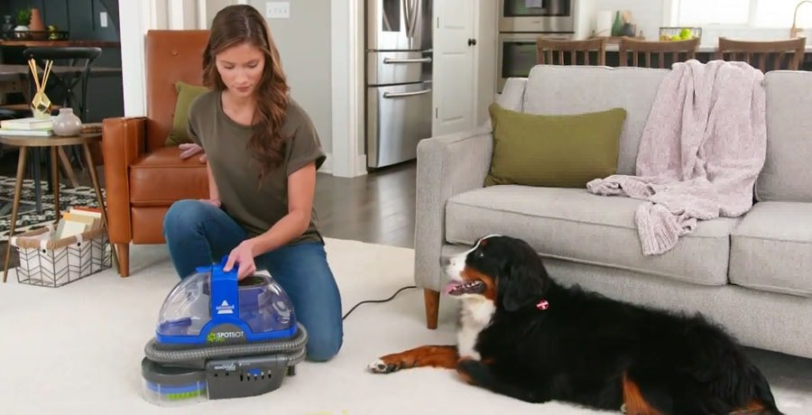 A woman cleans the carpet using an upholstery cleaner.