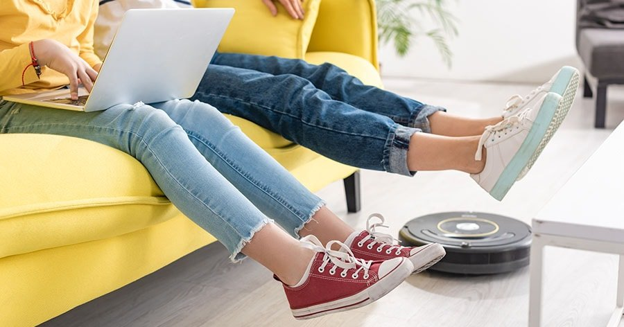 A robot vacuum cleaning the floor near the sofa and the young couple sitting on the sofa