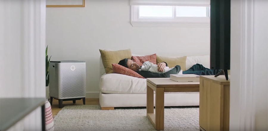 A man sleeping on a couch and a Airmega 400 standing nearby.