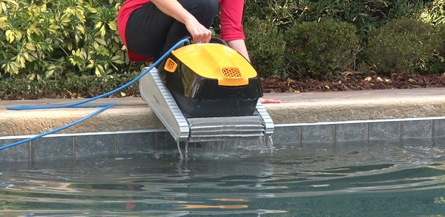 A woman takes the pool robot out of the water