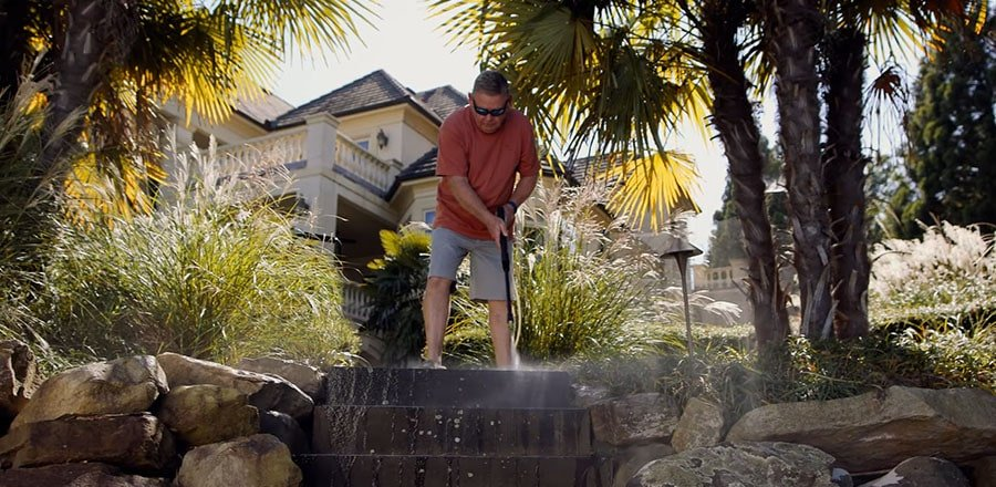 A man cleans the yard with the Greenworks electric pressure washer.