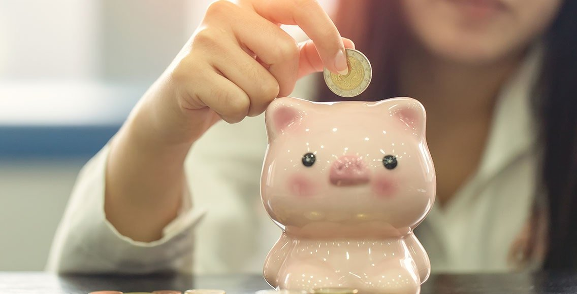 Young woman puts a coin into the piggy bank.