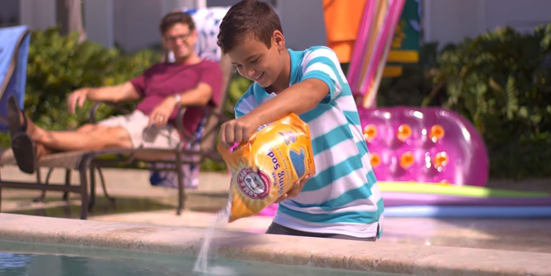 A boy adding baking soda to the swimming pool water