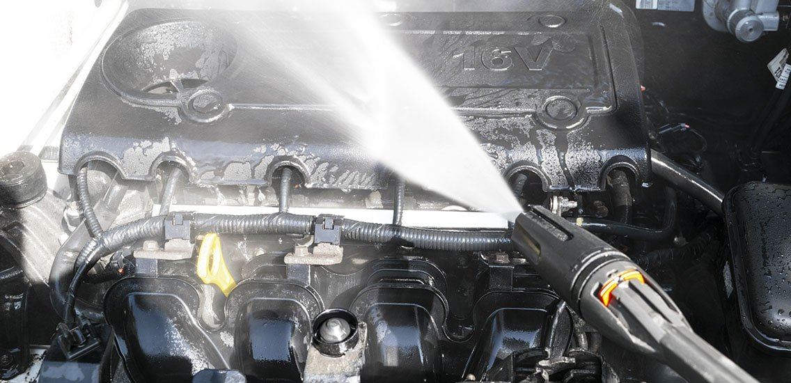 Man washes his car engine.