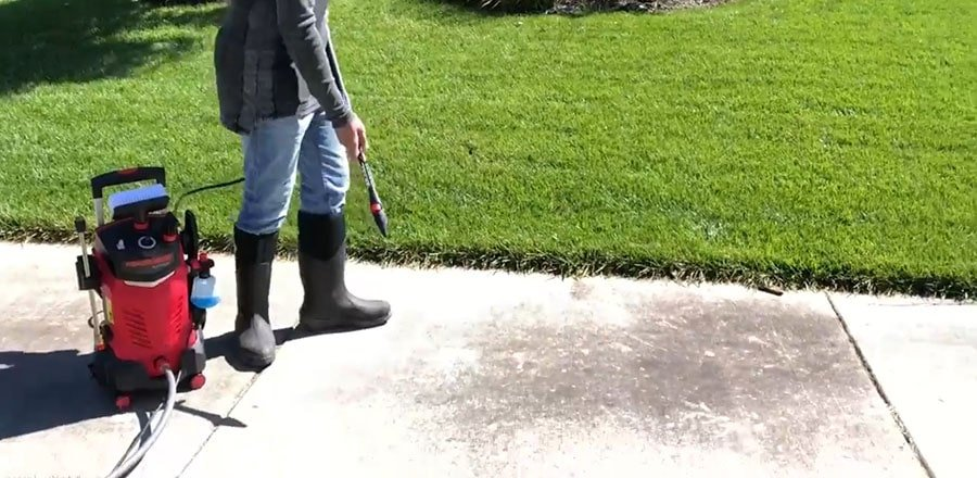 Man washes a sidewalk with the pressure washer