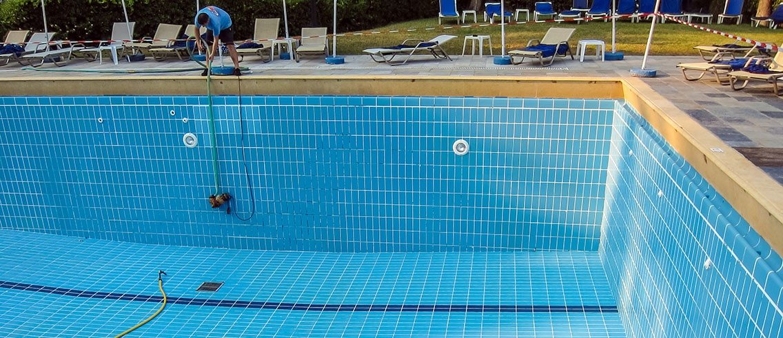 Man drains the pool for maintenance.