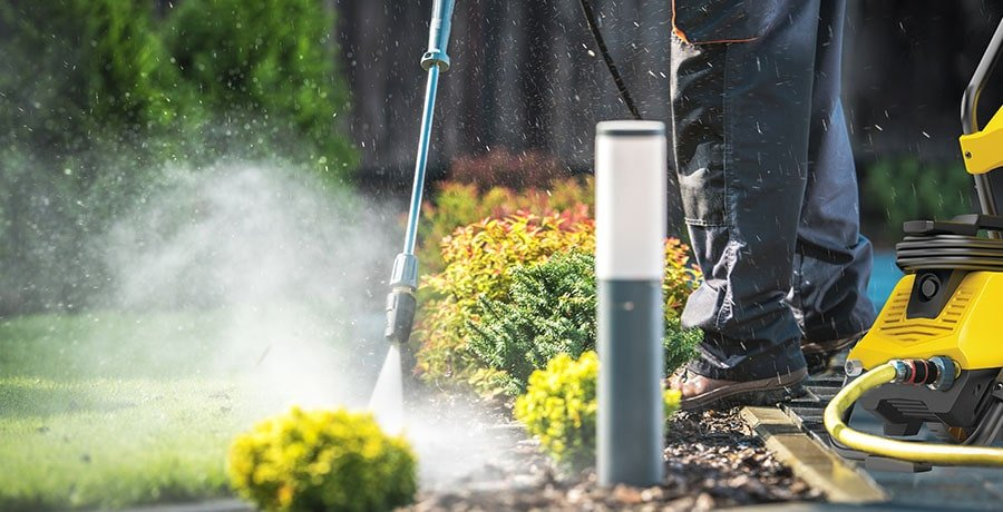 A man cleans the yard with the electric pressure washer from Stanley.