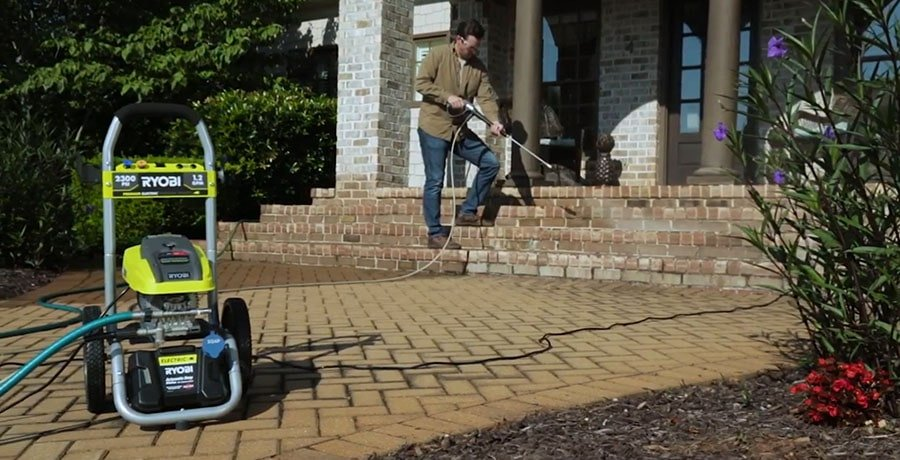 A man washes the front walkway of his house with the help of electric pressure washer from Ryobi.